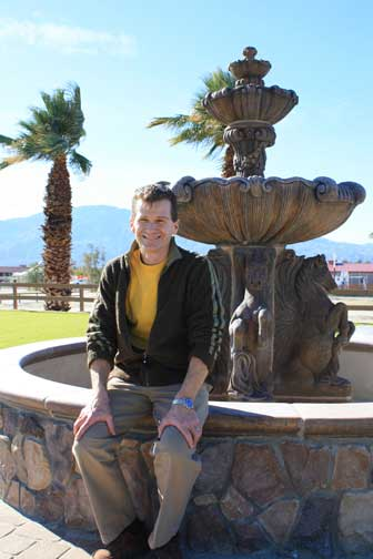 Portrait of Tom Struzzieri sitting on a fountain at the HITS Desert Horse Park.