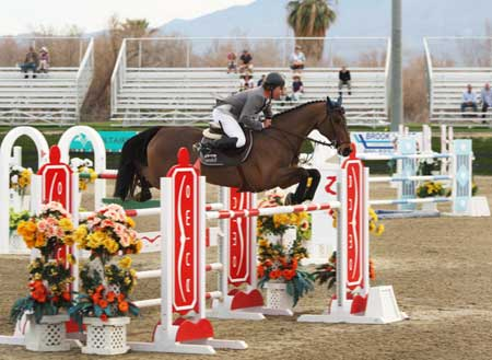 Markus Beerbaum and Lancero clear a bright red and white oxer.